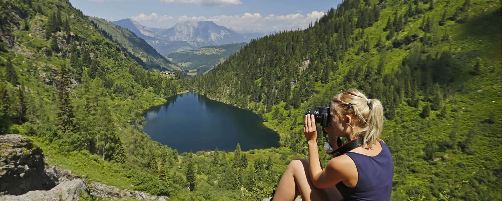 Woman taking a photo during a hike in the Schladming-Dachstein region